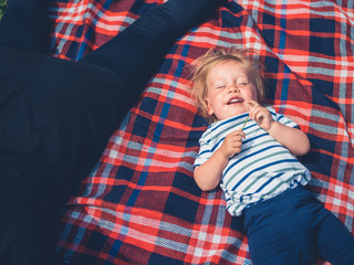Cute little boy having great time on picnic blanket