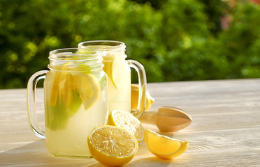 Two mason jar glasses of homemade lemonade, slices of organic ripe lemon, whole and halved, mint, juicer on white wooden table, country side tree foliage background. Close up, top view, copy space.