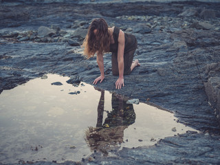 Young woman by rock pool on coast at sunset