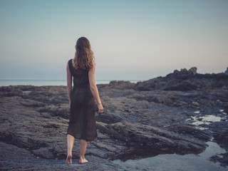 Young woman walking on coast at sunset