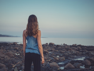 Young woman standing on coast at sunset