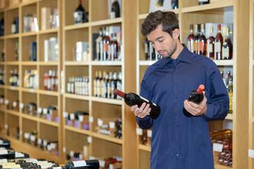 male choosing between two bottles of wine