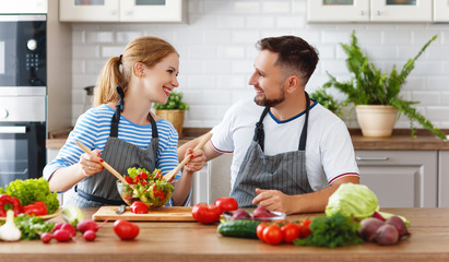happy family couple preparing vegetable salad in kitchen.