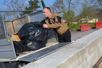 Worker emptying rubbish bags from vehicle