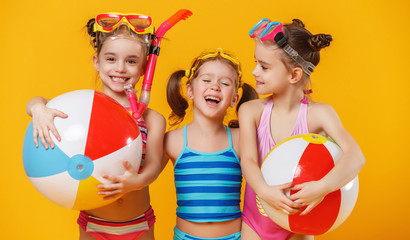 funny funny happy children in bathing suits  jumping  on colored background