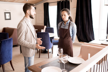 Displeased handsome restaurant manager with beard reporting young waitress in apron and gesturing while explaining her mistakes in modern establishment
