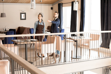 Serious confident successful young male manager in formal jacket gesturing while showing place for furniture while preparing restaurant room for event, serious waitress standing near him