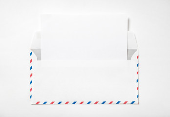 Open envelope with a sheet of paper. Blank airmail envelope with  empty template letter on a white background . Back view