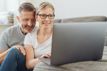 Affectionate middle-aged couple using at a laptop