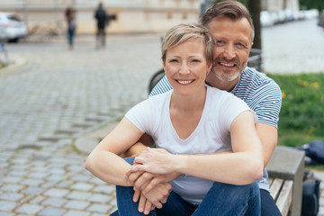 Happy middle-aged couple sitting on an urban bench