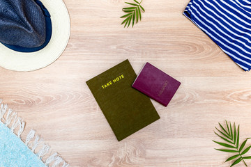 Top view of vacation accessories with passport, copy space and summer beach items. Lay flat fashion background on wooden floor.