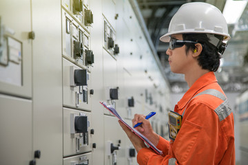 Offshore oil and gas maintenance daily activity, Electrical and Instrument technician logging data in electrical switch gear room.