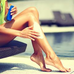 Woman applying sunscreen on her leg