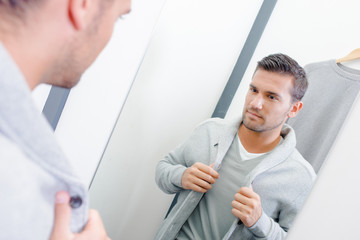 Man trying on jacket in fitting room