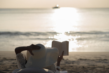Woman with white hat sit on the beach reading the booking during sunset.