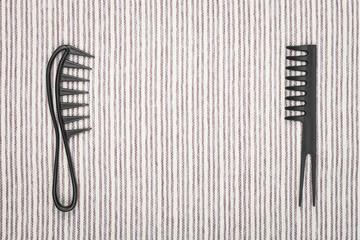 two different hairbrushes lying opposit to each other on a grey striped background. concept of professional hairdresser tools. free space for text