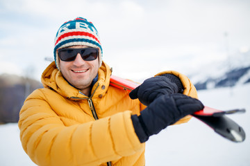 Picture of smiling man with mountain skis