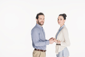 side view of married couple holding hands and looking at camera together isolated on white