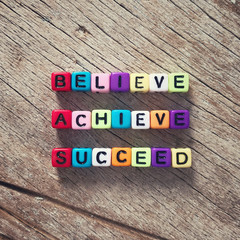 Inspirational quote - 'Believe, achieve, succeed' on colorful decorative beads. With vintage styled background.