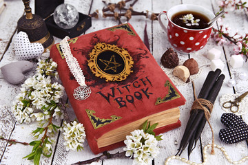 Witch book with black candles, cup of tea and mystic decorations. Occult, esoteric and divination still life. Halloween background with vintage objects