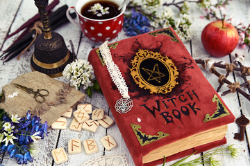 Red witch book with runes, mystic objects and cup of tea on wooden table. Occult, esoteric and divination still life. Halloween background with vintage objects