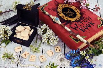 Runes in black box with witch book, magic wand and wildflowers on table. Occult, esoteric and divination still life. Halloween background with vintage objects