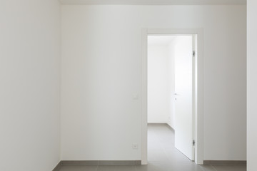 Detail of open doors in all-white apartment