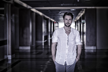 Waist Up Portrait of Attractive Young Man Wearing Shirt Standing Looking Thoughtful in Hallway of School or Shopping Mall