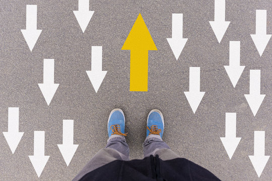direction arrows on asphalt ground, feet and shoes on floor