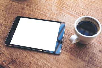 Top view mock up image of black tablet with white blank desktop screen and coffee cup on vintage wooden table in cafe