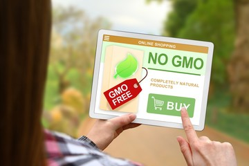 No GMO concept, girl holds the digital tablet on blurred nature background