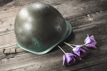 military helmet and flowers on a wooden background. the concept of memory of the heroes of war.