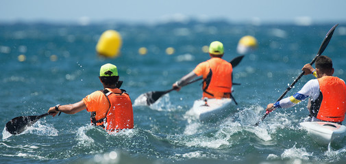 Paddlers race their ocean kayak surf skis through breaking waves