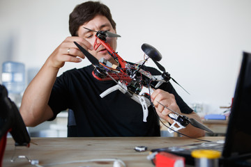 Image of man fixing square copter at table