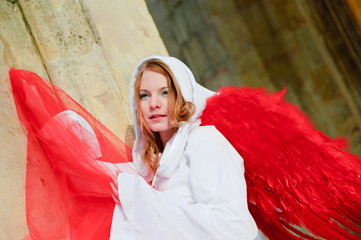 young blonde in a white canopy and red wings