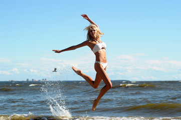 beautiful blonde in a swimsuit is jumping near the sea