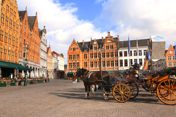 Old houses and horse carriages on Grote Markt square, Brugge, Belgium