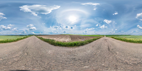 full seamless spherical panorama 360 by 180 degrees angle view on the old asphalt road among fields in sunny summer day with halo in equirectangular projection, skybox VR virtual reality content