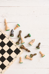 wooden chess figures and part of a chess board on white table background. Top view.