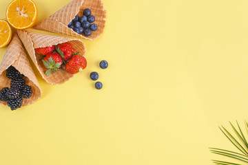Tropical fruits and berries on a yellow background. Free space for text. Vacation and relaxation. Copy space, Flat lay.