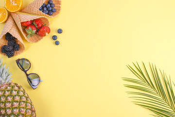 Tropical fruits and berries, and a palm branch on a yellow background. Free space for text. Vacation and relaxation Flat lay, copy space,