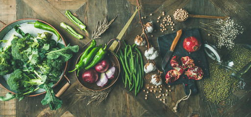 Wall Mural - Winter vegetarian, vegan food cooking ingredients. Flat-lay of seasonal vegetables, fruit, beans, cereals, kitchen utencils, dried flowers, olive oil over wooden background, top view, wide composition