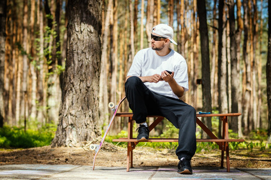 man in a white hat with a skateboard sits on a picnic table and uses a phone in a summer park