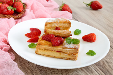 Sweet tasty puff pastry dessert on a plate on a wooden background. Delicious homemade cookies with strawberry jam, berries and sugar powder