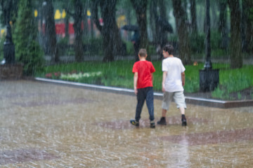 Two boys are walking under a pouring rain. Blurred image