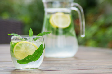 Fresh homemade lemonade with ice and mint on the table.