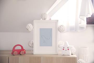 Stylish nursery interior with mock up photo frame , cotton lamps, star and red car toy. White and sunny background wall.