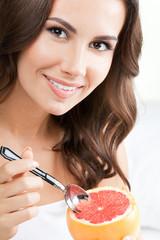 Smiling woman eating grapefruit at home