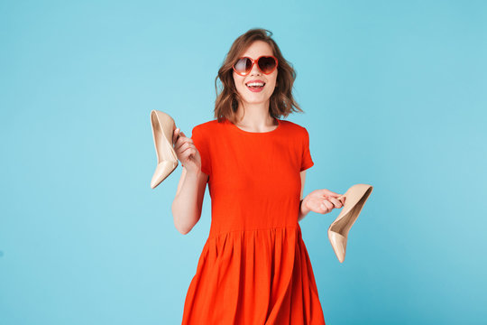 Young smiling lady in dress and heart sunglasses standing with classic shoes in hands on over blue background