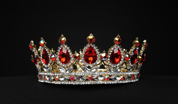 portrait of a beautiful jewelled ruby, diamond and golden crown, photographed on a black studio background.